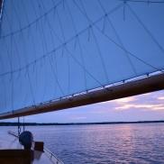 Selina II's sail against a blue and purple twilight sky.