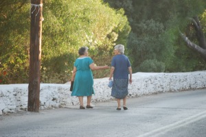 Two Yia Yias walk down the hill to the port.