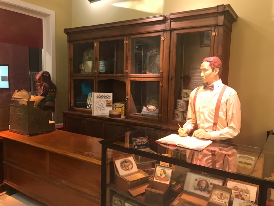 A lesson on the history of cigar advertising in a cigar shop